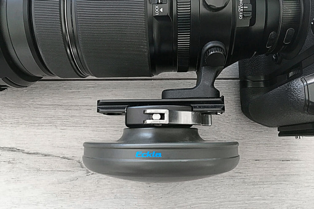 Side view of the ECKLASPHERE attached to to big lens and camera body. The photography equipment is lying on the ground