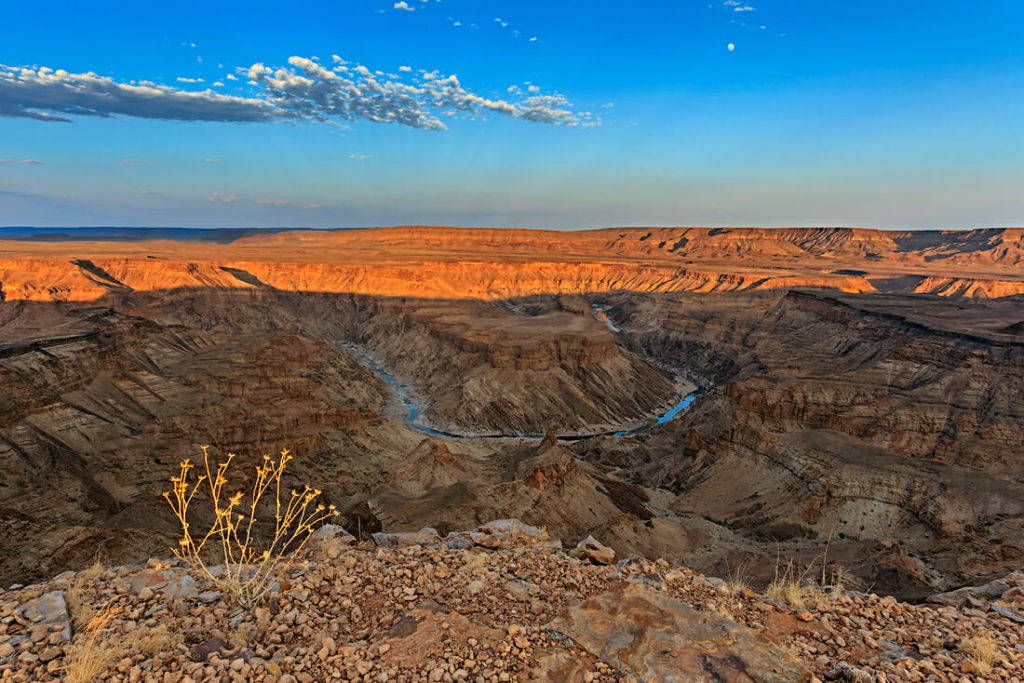 Fish river canyon main view into the valley. Water is in the river. In sky some clouds and a nearly full moon, Namibia