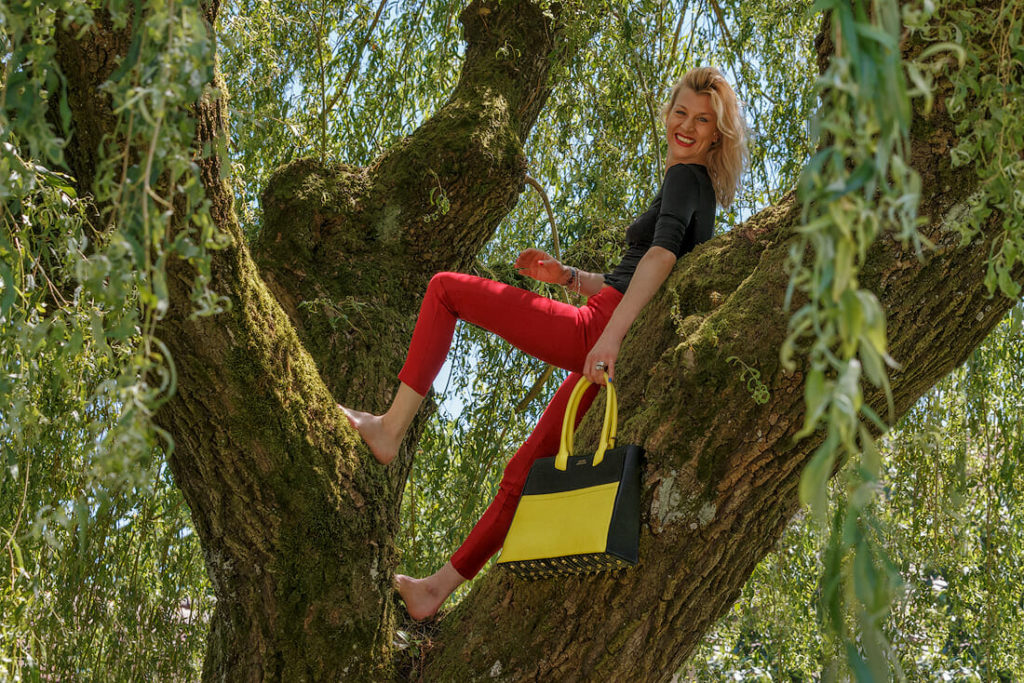Karen Olivo standing on a tree with a yellow black Tote from Luc8k customized leather bags.