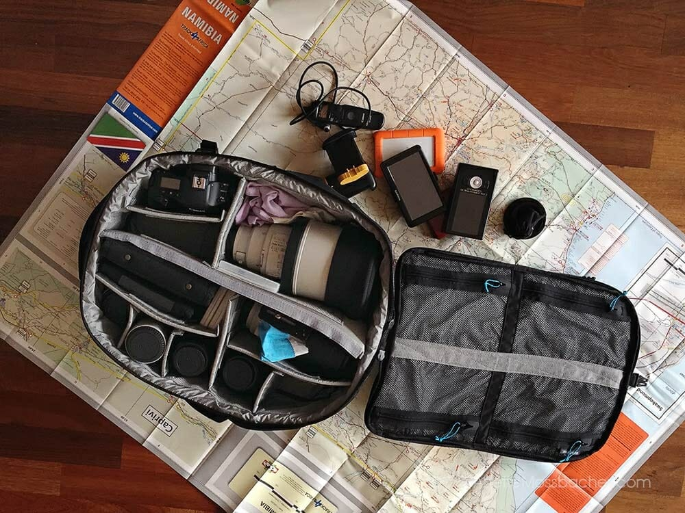 Camera bag of a landscape and wildlife photographer, inside with big lens, smaller lenses photo gear, including map for a trip to Africa.