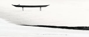 Beautiful canoe stands on stilts at the riverbank of Brahmaputra river on stilts. Fine art B&W photo. (copyright Anette Mossbacher)