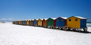 Beautiful colorful beach huts are lined along the beach Muizenberg. In front takes a woman a shower. (copyright Anette Mossbacher)
