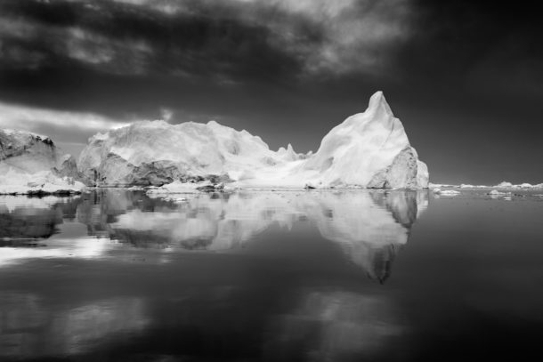 A colossal iceberg floats in the Arctic sea. Its reflection shows beautifully in the calm water. (copyright Anette Mossbacher)