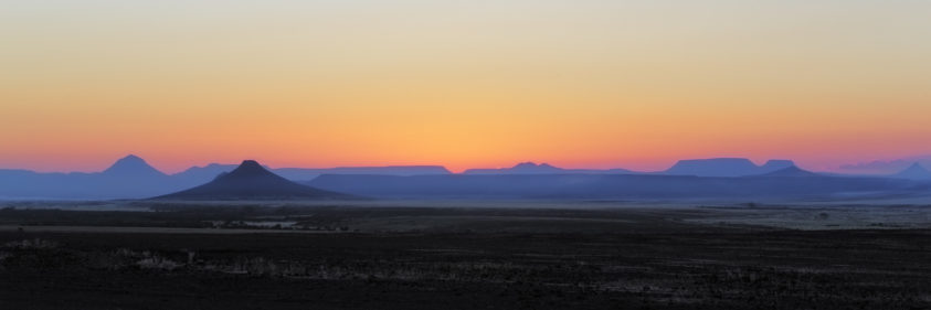 A beautiful desert sunrise a spectacular. Behind the mountain range of the Skeleton coast, the sun comes up. (copyright Anette Mossbacher)