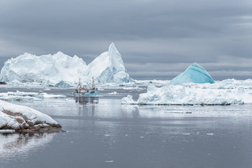 A Fisher boat is sailing through the icebergs in the Disko Bay. The fisher boat with massive icebergs. (copyright Anette Mossbacher)