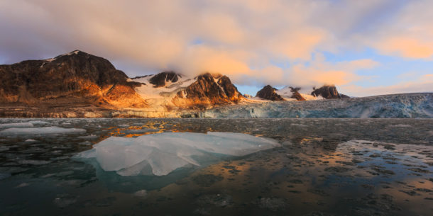 Fuglefjorden glacier flowing into the Arctic sea. The rising sun lights the tips of the mountains softly. (copyright Anette Mossbacher)