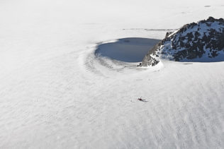 A helicopter is standing on a glacier, quite small in comparison to the expanse of ice surrounding it. (copyright Anette Mossbacher)