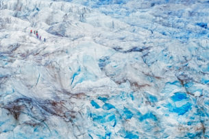Hikers climb a massive glacier in Svalbard. TA  group of people is hiking in the upper left-hand corner. (copyright Anette Mossbacher)