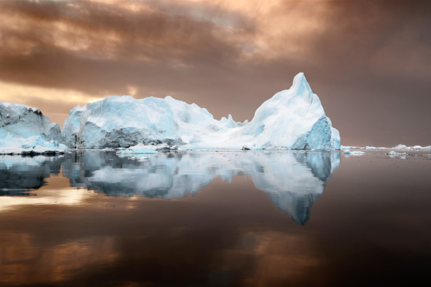 The colossal iceberg with reflection floats in the water of the coast of Ilulissat, Greenland. (copyright Anette Mossbacher)