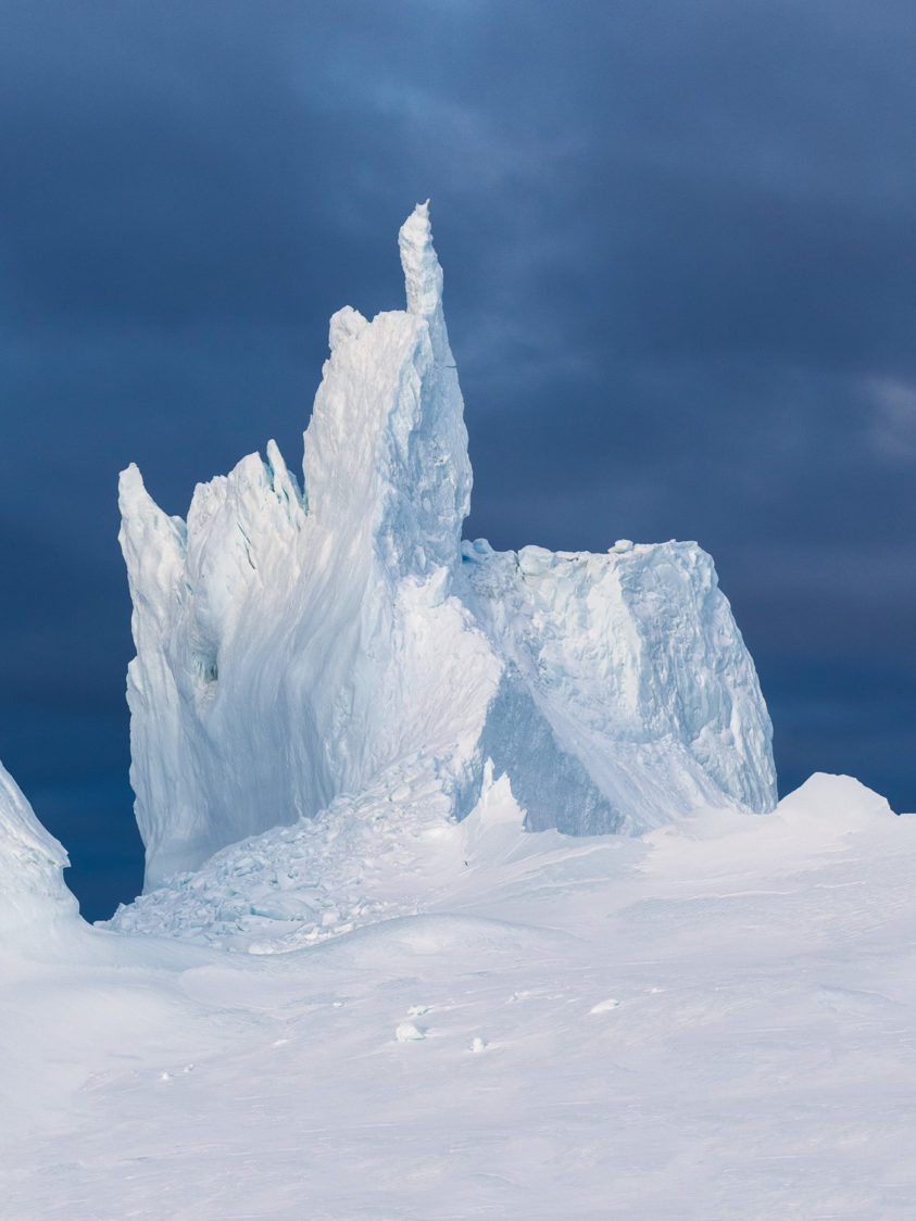 That magnificent iceberg contrasts against the dark blue, cloudy sky — a pillar within its unique shape. (copyright Anette Mossbacher)