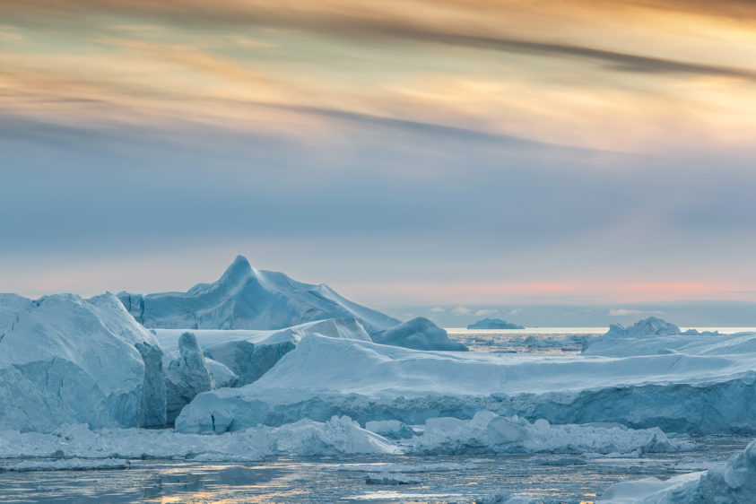 Colossal icebergs are floating at sunset in the Disko Bay. The soft pastel colors complement the ice. (copyright Anette Mossbacher)