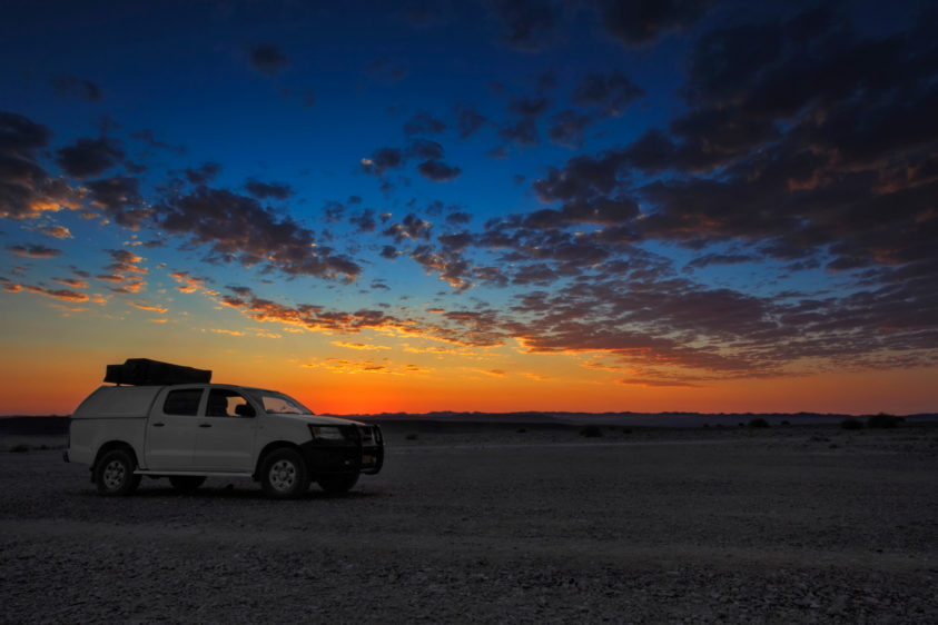A jeep stands in the vastness of a desert at sunrise — a gorgeous sky with glowing, vibrant colors. (copyright Anette Mossbacher)