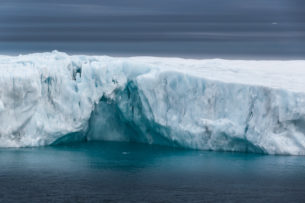 A large iceberg has many crevices in its structure. The dark blue sea contrasts the ice. (copyright Anette Mossbacher)