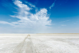 That landscape photograph shows the endless Makgadikgadi salt pans and beautiful clouds in the sky. (copyright Anette Mossbacher)