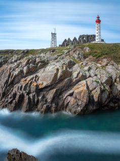 On top of a cliff rises the Lighthouse Pointe Saint Mathieu, which is surrounded by soft moving clouds. (copyright Anette Mossbacher)
