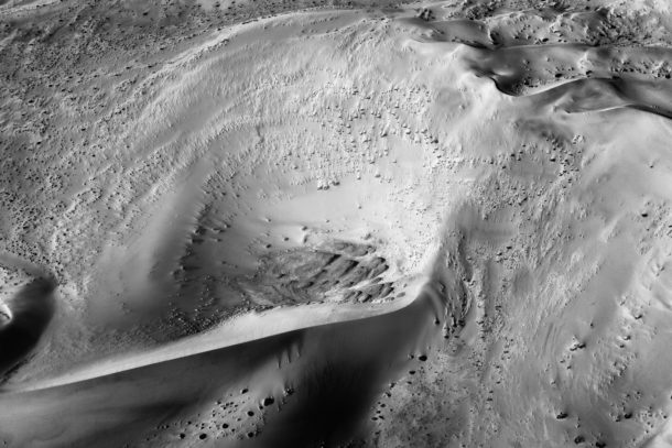 A B&W fine art desert areal photograph shows massive dunes and an enormous crater. (copyright Anette Mossbacher)