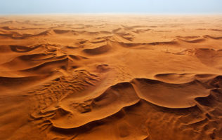 In this colorful areal landscape photograph, beautiful patterns show in the red sand of the dunes. (copyright Anette Mossbacher)