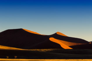 A desert landscape photograph shows the gorgeous African sunrise. Light returns to Sossusvlei. (copyright Anette Mossbacher)