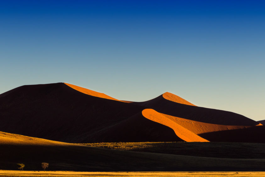 A desert landscape photograph shows the gorgeous sunrise. Light returns to Sossusvlei. (copyright Anette Mossbacher)