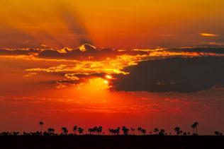 A sunset landscape photograph of the Makgadikgadi Salt Pan. Storm clouds above largest pans on earth. (copyright Anette Mossbacher)