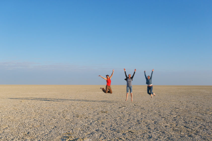 Three women jump in the air at the same time on the Etosha salt pan. All three women raise their arms. (copyright Anette Mossbacher)