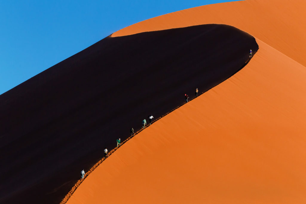 Tourists climb the highest dune #45 at sunrise in a line. Behind the dune, you see the blue sky. (copyright Anette Mossbacher)