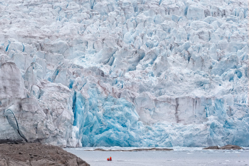 A zodiac is driving with people in front of the Nordenskiold glacier in Svalbard. (copyright Anette Mossbacher)
